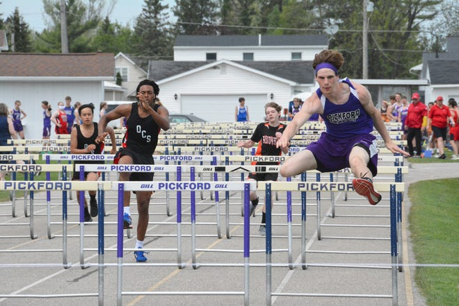 Pickford's Josh Sullivan, right, won the 110 hurdles at the Eastern UP Conference track and field meet Thursday. The Pickford boys and girls also claimed team titles in the EUPC.