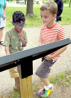 """Coy Yunker, right, was excited when he found his poem on display at Thurston Woods Park during a student reception for """"Poetry Walk."""" He views the poem with friend Chethan Blaine, who also has poetry featured at the exhibit."""