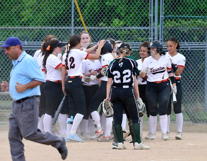 The Taunton High softball team greets Tiger shortstop Hanna Aldrich at the plate after Aldrich belted a home run against Mansfield.