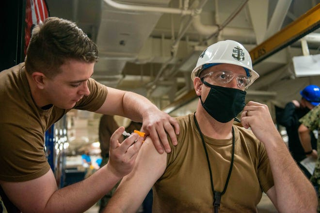 Hospitalman Henry Mason, of Uhrichsville, assigned to the aircraft carrier U.S.S. George Washington, has given out COVID-19 vaccines. Pictured, from left: Henry Ross and Chief Aviation Support Equipment Technician Andrew Couillard.
