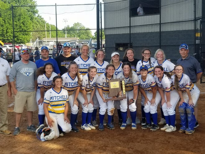 The Mitchell softball team holds up its trophy after defeating Providence for the Clarksville Sectional title on Thursday. It was the program's first title since 1994.