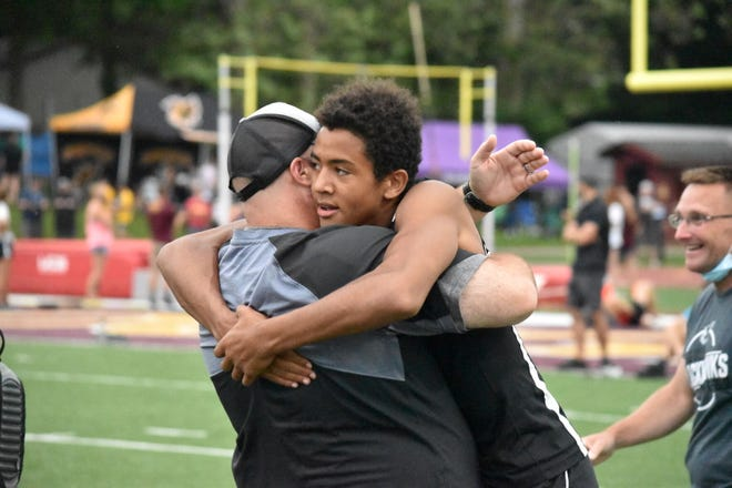 Springs Valley coach Derek Freeman embraces Blackhawk junior Conner Grimes after the latter qualified for the State Finals by finishing third in the 100-meter dash. Grimes would also go on to qualify in the long jump, again finishing third.