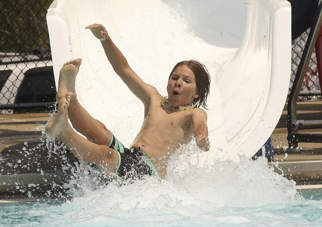 Jaymee Reed takes a trip down the water slide at the John Lowery Municipal Pool. in this 2017 file photo. A shortage of certified lifeguards is affecting municipal pools. The Bedford pool will open June 4.