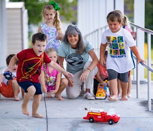 Kindergarten teacher Paula Jones enjoys some play time outside with her students at Waller Elementary on their last full day of school on May 27.