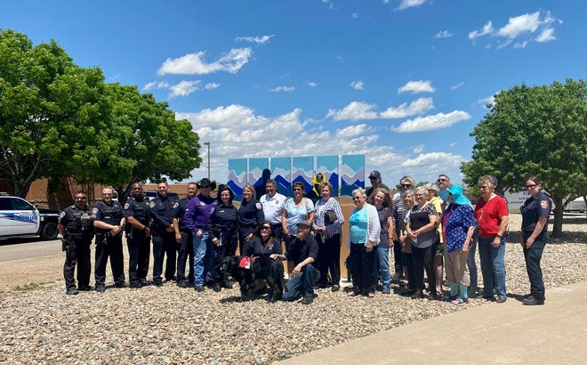 The Pueblo West Women's League, first responders, and artist of the sculpture Eric McCue stand in front of the sculpture 'Every Day Heroes' Tuesday May 25, 2021.