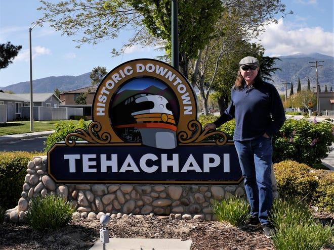 John stands next to the Historic Downtown Tehachapi sign in Tehachapi, Calif.