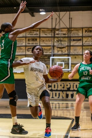 Hesperia's Queen Allah drives towards the basket while guarded by Victor Valley's Jewel Rencher, left, Thursday night.