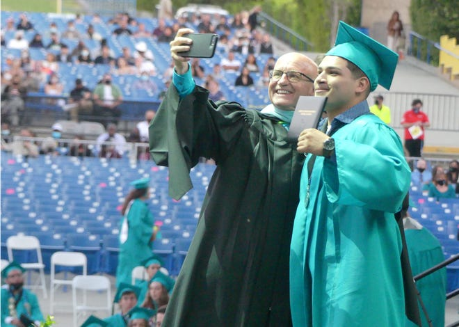 Sultana High School Principal Larry Bird takes a selfie with a graduating senior on Thursday, May 27, 2021, during the school's 25th commencement ceremony at Glen Helen Amphitheater in Devore.