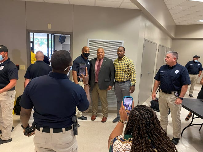 People take photos with Ronney Howard (center) after the 30-year veteran was named chief of the Alexandria Police Department on Friday afternoon. Howard has been the interim chief since November 2020.