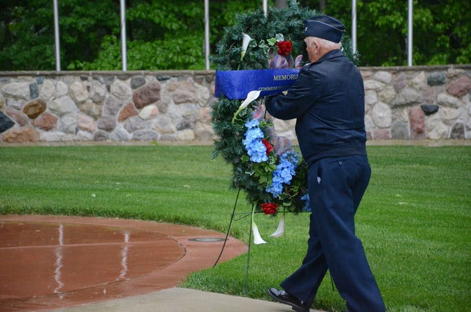 Retired Air Force Colonel Frank Walker places a wreath Friday at Fort Custer National Cemetery to commemorate Memorial Day.  (Trace Christenson/The Enquirer)