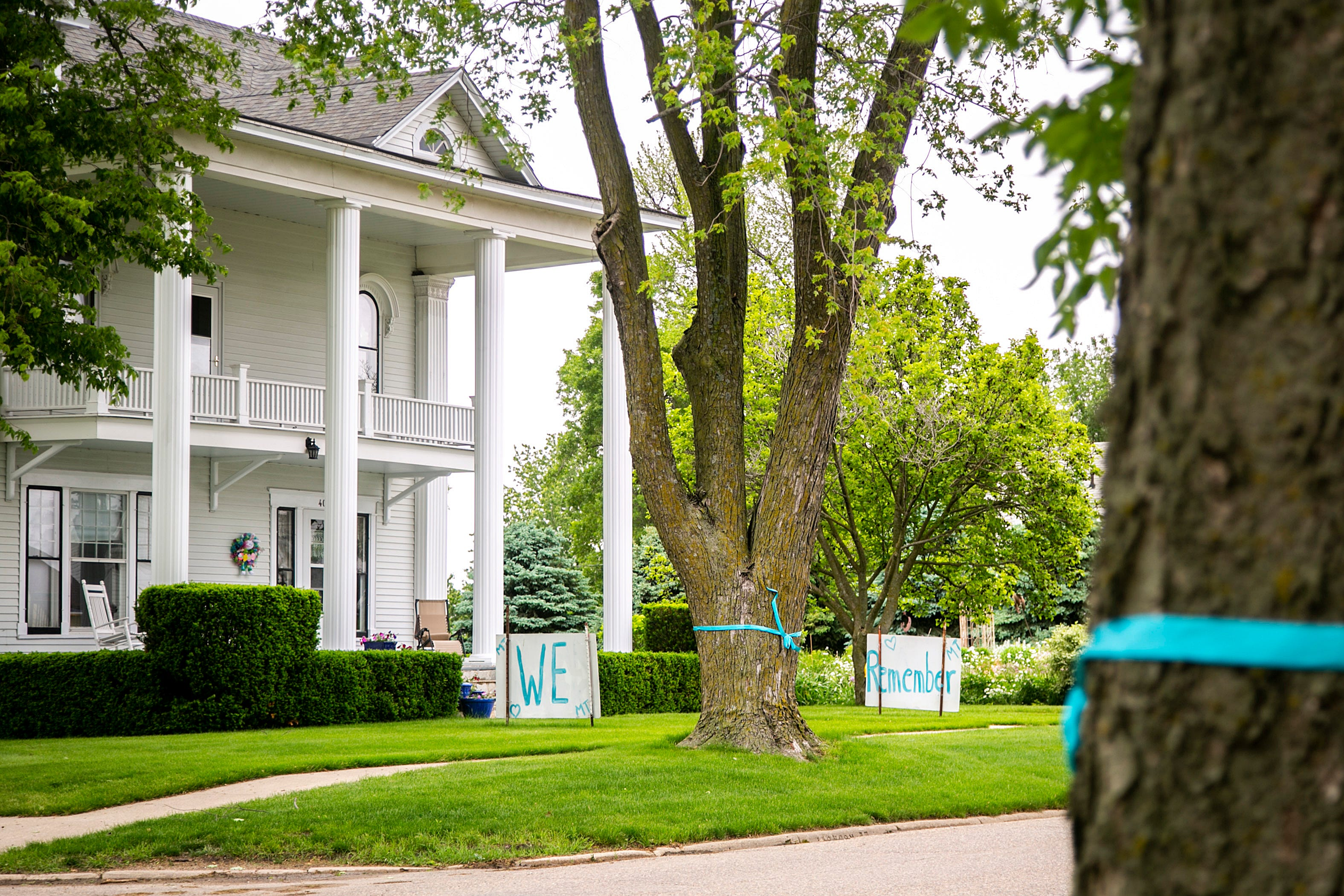 """Teal ribbons, in honor of Mollie Tibbetts, are attached to trees along Jackson Street in front of a house with signs reading """"We remember,"""" Friday, May 28, 2021, in Brooklyn, Iowa."""