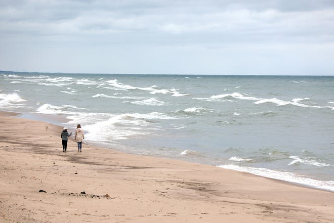 People walk along the Lake Michigan beach near a cottage that Heather Gradowski, owner of Pineapple Vacations, manages for clients who rent them out to vacationers.