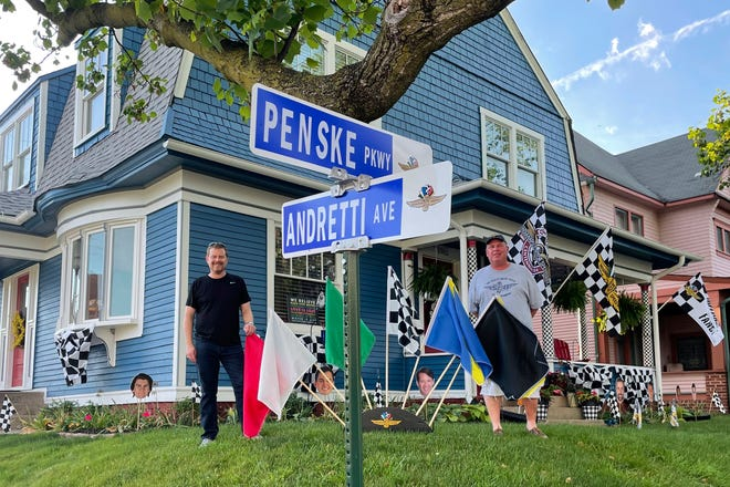 Chris Otto, left, of Seattle, and his brother Eric Otto, pose outside Eric's home, decorated for the Spectacle of Homes contest to be featured ahead of the Indianapolis 500 auto race, Thursday, May 27, 2021, in Indianapolis.