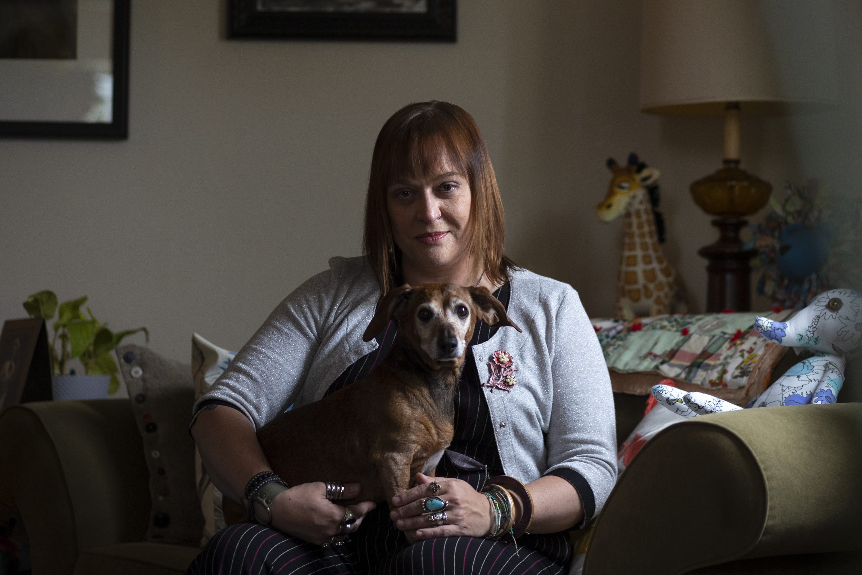 Stacey Burkhart, head of SAGE Green Bay, and business owner of Eight Trees poses for a portrait with her dog Daisy in her apartment, Thursday, May 27, 2021, Pulaski, Wis. Samantha Madar/USA TODAY NETWORK-Wisconsin