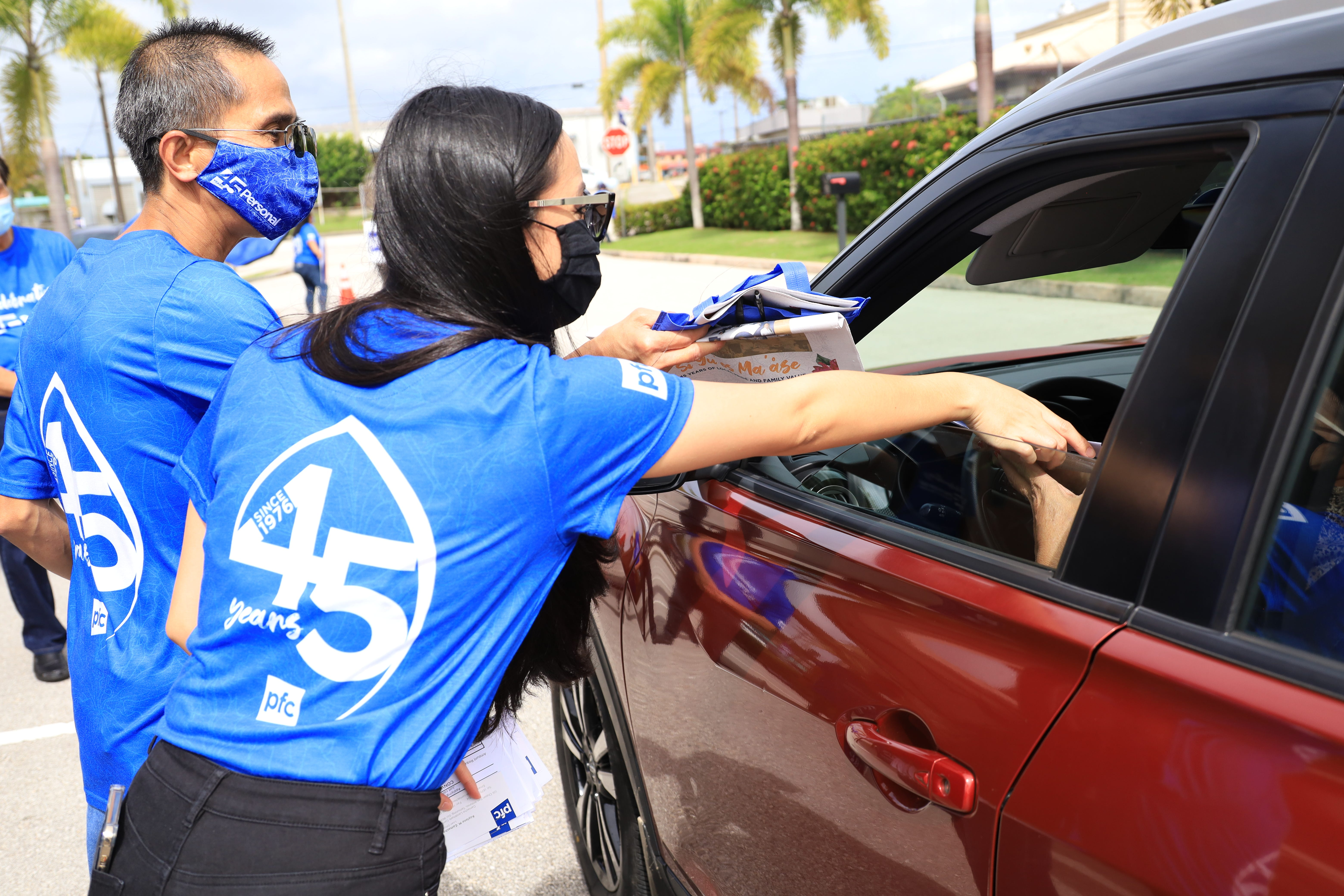 Employees of Personal Finance Center in Tamuning hand out goody bags during the company's 45th anniversary on Thursday, May 29, 2021.