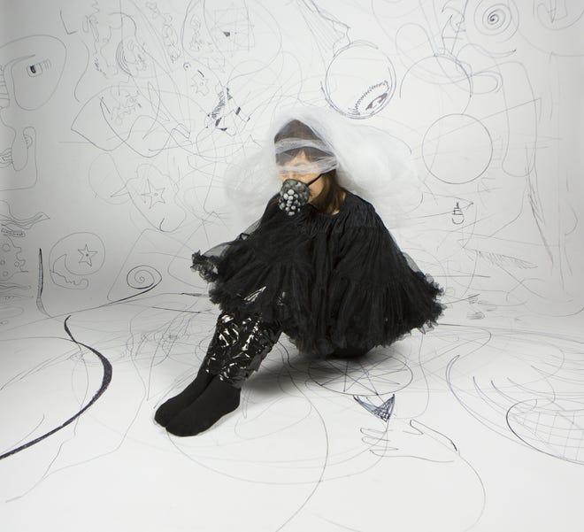 "Iowa City artist Satomi Kawai photographed demonstrating her wearable art piece, ""Always on the Quiet Side."""