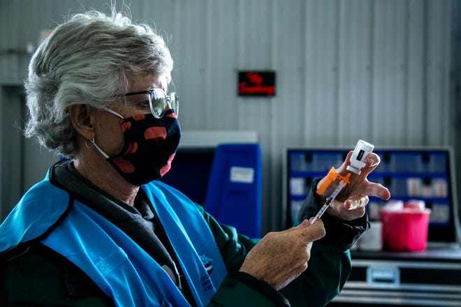 Kelly Smith, a Johnson County Public Health nurse, draws a dose of the Moderna COVID-19 vaccine during a free food box and vaccine clinic drive-thru event, Thursday, May 27, 2021, at the Johnson County Fairgrounds in Iowa City, Iowa.