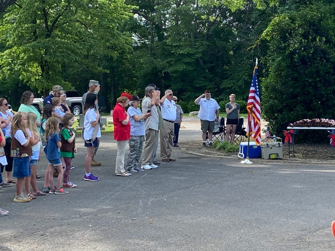 """Veterans and other attendees at a Memorial Day ceremony at Ridgecrest Cemetery stand at attention during the playing of """"Taps."""""""