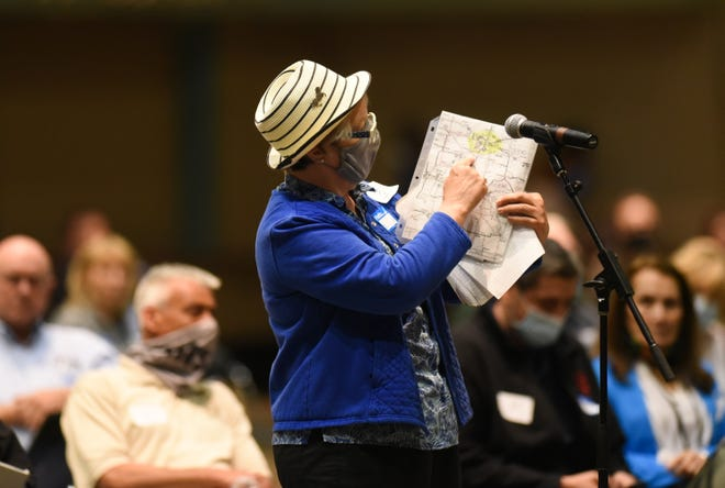 A woman displays a map showing lines of her voting district Thursday, May 27, 2021, during the Michigan Independent Citizens Redistricting Commission meeting at the Lansing Center.