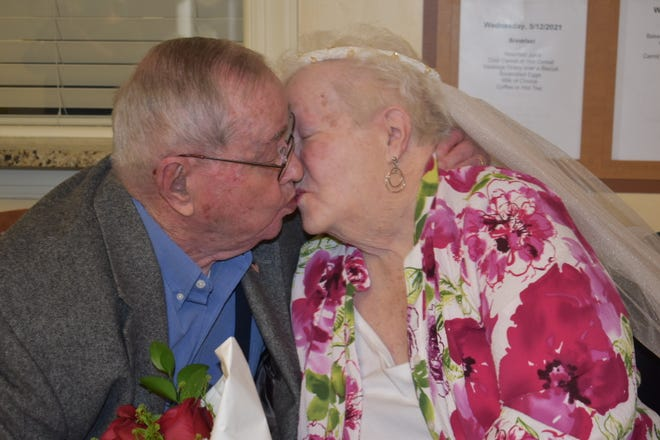 Leroy Dean, 88, and Marilyn Dean, 86, kiss during a vow renewal ceremony at Community Care and Rehabilitation on May 12.