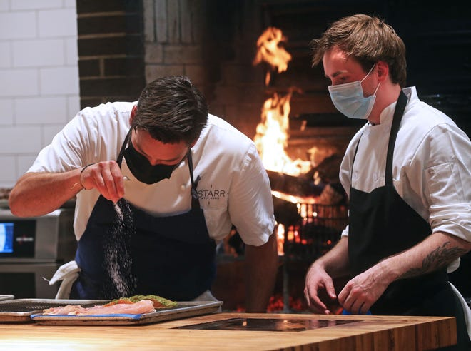 Kyle Knall, left, seasons food during preparation, while cook Sam Galaszewski watches on May 27 at the soft opening of Birch at 459 E. Pleasant St. in Milwaukee.