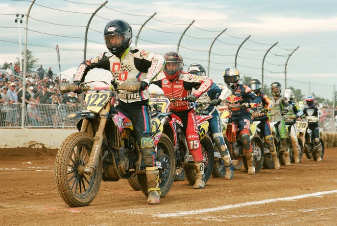 """Riders await the start of a district flat-track motorcycle race in a still image from """"Race Night,"""" a documentary from filmmaker Sean Jackson on the sport, the competitors and their families."""