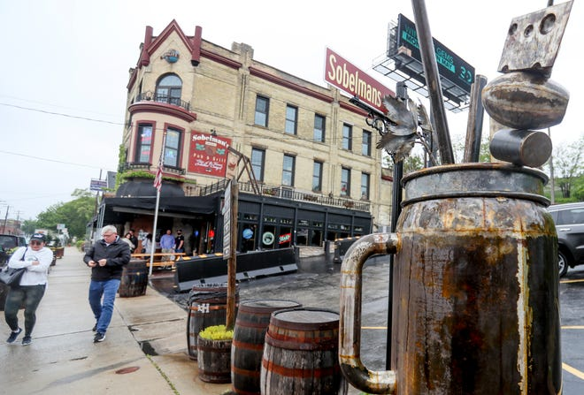 Tuyen and Tom O'Day pass by the new 6-foot-tall, 400-pound bloody mary sculpture Friday outside Sobelman's Pub and Grill in Milwaukee. The sculpture was created by local blacksmith Kent Knapp.