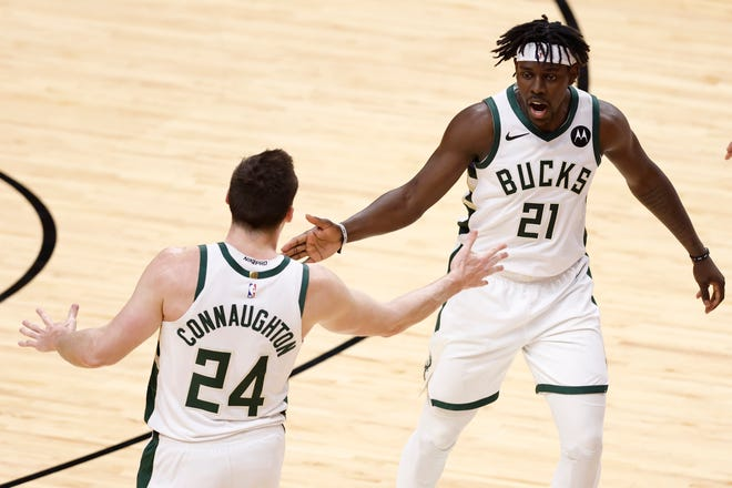 Bucks guards  Jrue Holiday and  Pat Connaughton celebrate a basket in the third quarter Thursday.