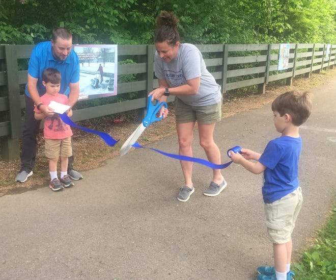 """Jeff Rothweiler, Director of the Pataskala Public Library, and Southwest Licking Schools' Suzanne Hayes cut the ribbon, officially opening the 2021 """"Story Trail"""" with the help of Rotherweiler's twin sons, Keegan and Keaton."""