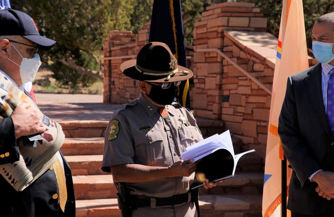 Navajo Criminal Investigation Services Director Michael Henderson, center, looks through an assessment of the Navajo Police Department on May 27. The report was released during an event in Window Rock, Arizona.