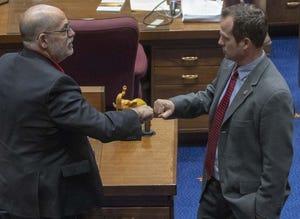 (From left) Sens. David Livingston, R-Peoria, and Warren Petersen, R-Gilbert, fist bump as the Arizona Senate prepares for a two-week break.