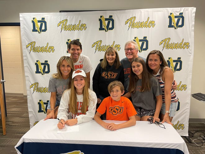 May 21, 2021; Grace Ping signs her Letter of Intent committing to Oklahoma State as her family stands behind her, including her mother and Desert Vista High School girls cross-country coach Megan Ping (far left) in Phoenix, Ariz.