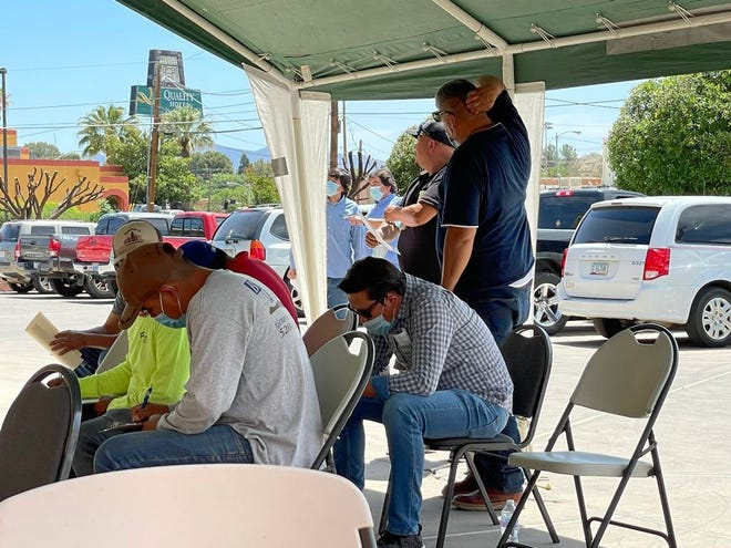 Commercial truck drivers who regularly cross the border to transport fresh produce and other items from Mexico to Arizona wait to get their vaccine outside the Mexican Consulate in Nogales.