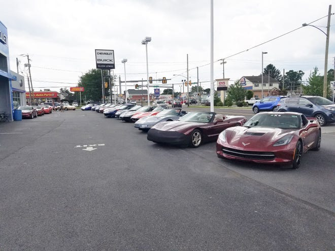 The Klick Lewis Concours is being hosted at a Chevrolet dealership. The C5 Corvette second from right is not wearing a car-sized face mask, but rather a car bra to protect from bugs.