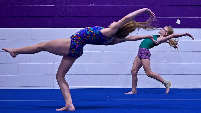 Students warm up before practicing on the uneven bars at the Texas Tumbleweeds Gymnastics facility Thursday, May 27, 2021.