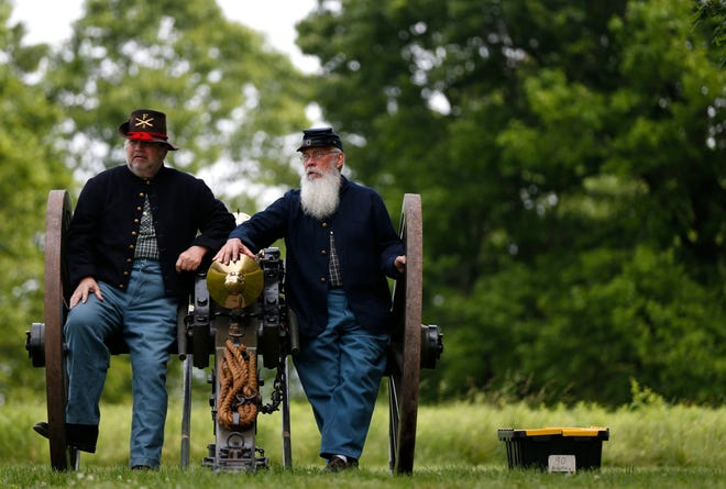 Civil War reenactors Tom Englin Fred Donnell sit on a cannon before a firing demonstration of it at a ribbon cutting for the Wilson's Creek National Battlefield visitor center on Friday, May 28, 2021.