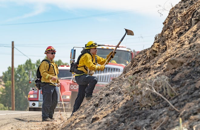 Firefighters from Tulare County and Orange Cove work a grass fire Thursday, May 27, 2021 that closed a small section of Highway 63 between Avenues 444 and 448. About 50 acres were scorched, the cause was under investigation.