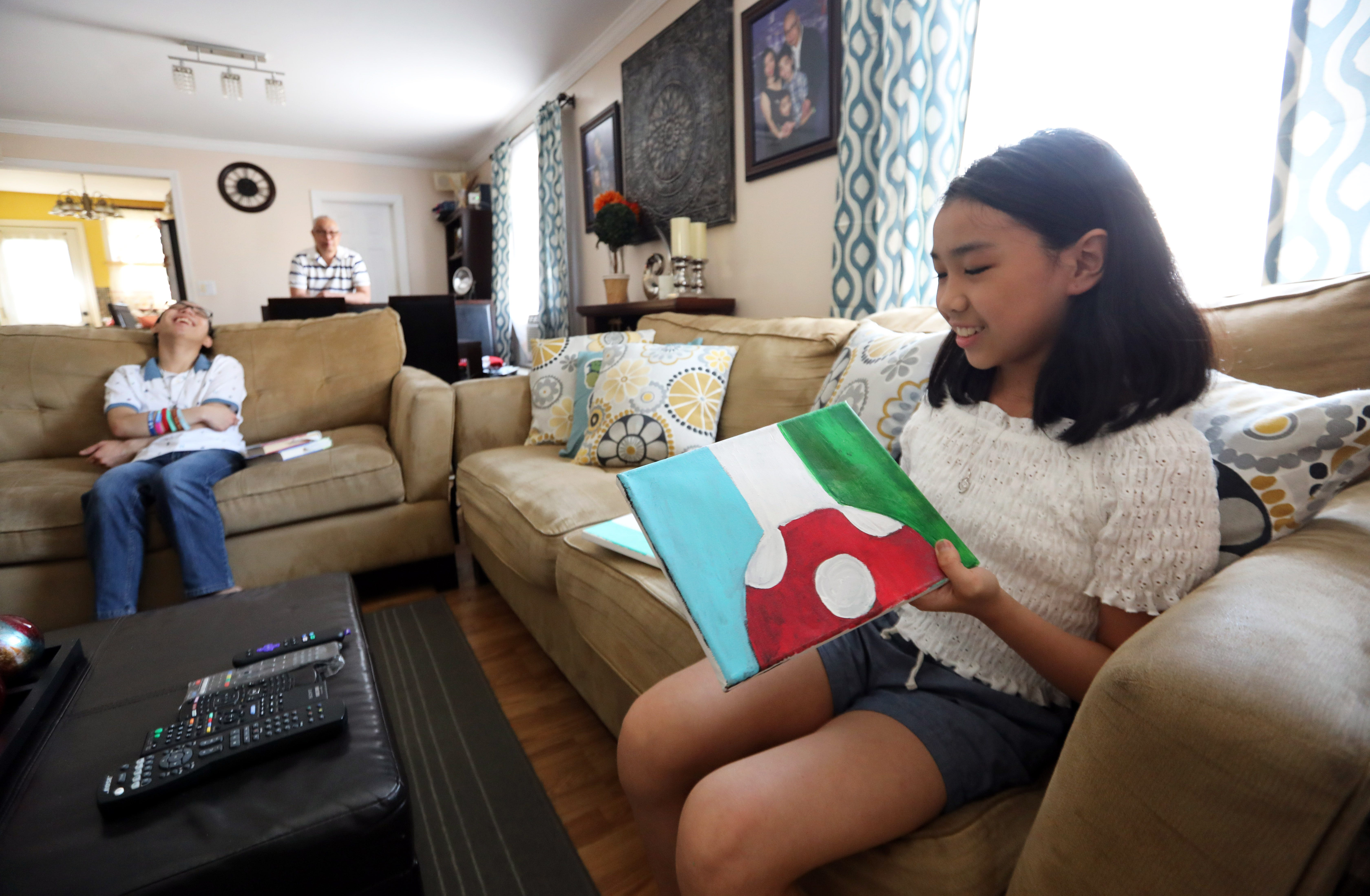 Julia Santiago, 11, has been painting more while at home during the pandemic. She shows some of her recent work at home in Mount Vernon May 27, 2021. Julia and her brother, Bryan, 17, have been remote learning since the pandemic began in March 2020.