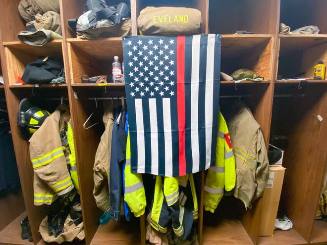 A thin red line flag covers Austin Eveland's locker at Station 3 of the Zanesville Fire Department. He worked at the ZFD for four years, and at Falls Township before that.