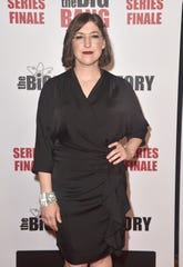 Mayim Bialik poses in front of a photographer at