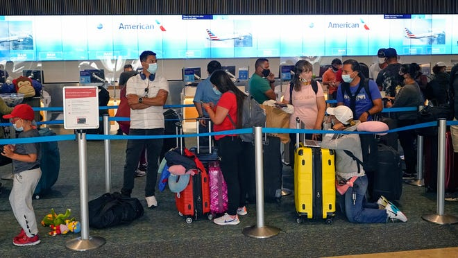 Travelers line up to check in at a ticket counter at the Orlando International Airport before the Memorial Day weekend Friday, May 28, 2021, in Orlando, Fla.
