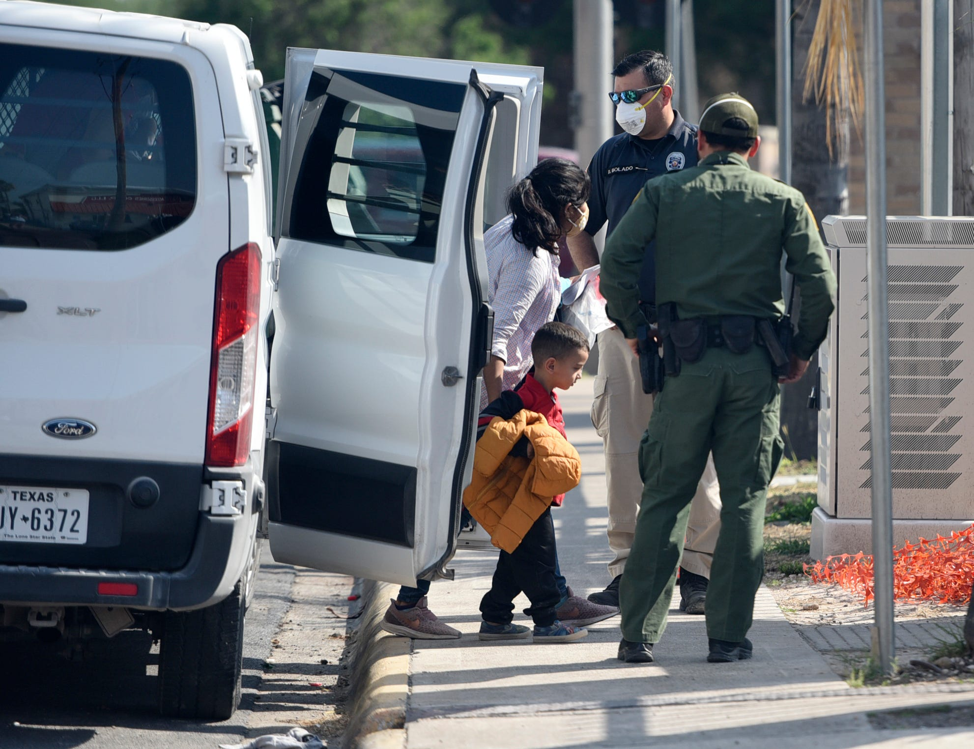 Migrants exit a Border Patrol van to get tested for the coronavirus April 9 in McAllen, Texas.