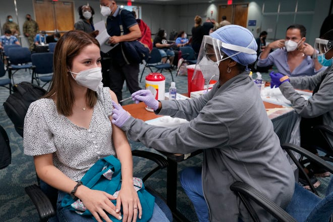 Natalia Dubom, of Honduras, gets the Johnson & Johnson COVID-19 vaccine on Friday at Miami International Airport. The vaccine will be offered to all arriving passengers through Sunday as part of a Florida Emergency Management Agency program.