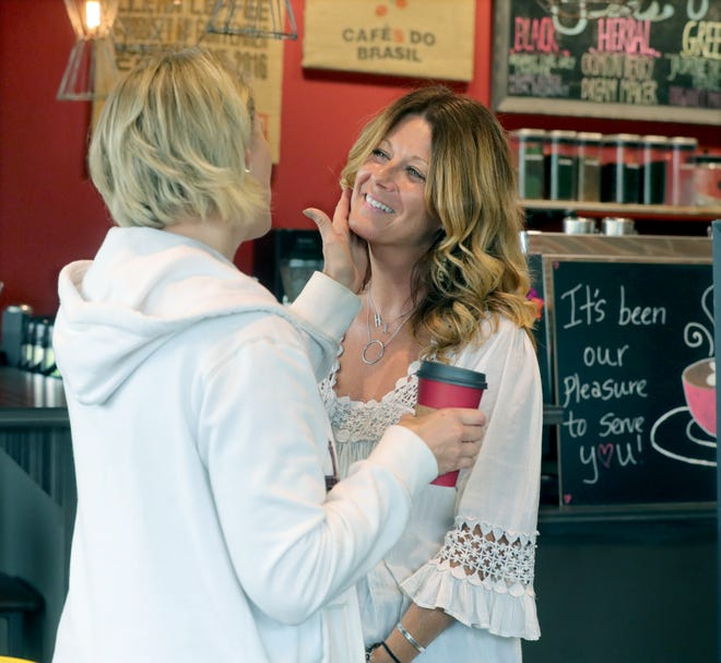 """Heather Lechiara, left, exchanges kind words with Corner Cup Coffeehouse owner Heather Ciranna during the shop's """"Next Chapter Bash"""" on Saturday, May 29, in Stow. [Phil Masturzo/ Beacon Journal]"""