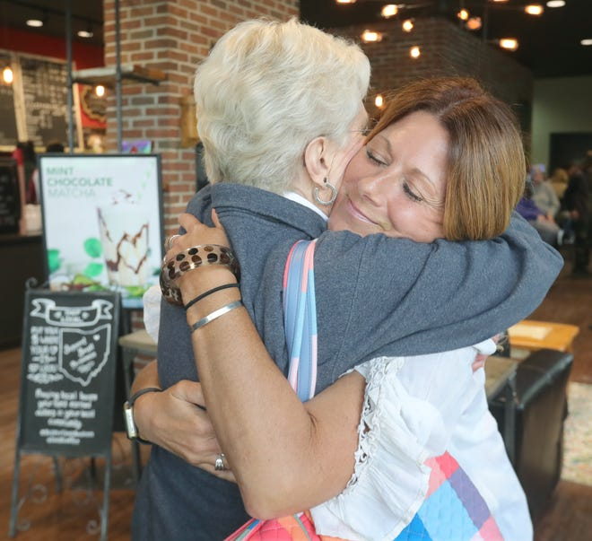 Corner Cup Coffeehouse owner Heather Ciranna gets a hug from her mother, Janet Blank, on Saturday, May 29 in Stow. [Phil Masturzo/ Beacon Journal]