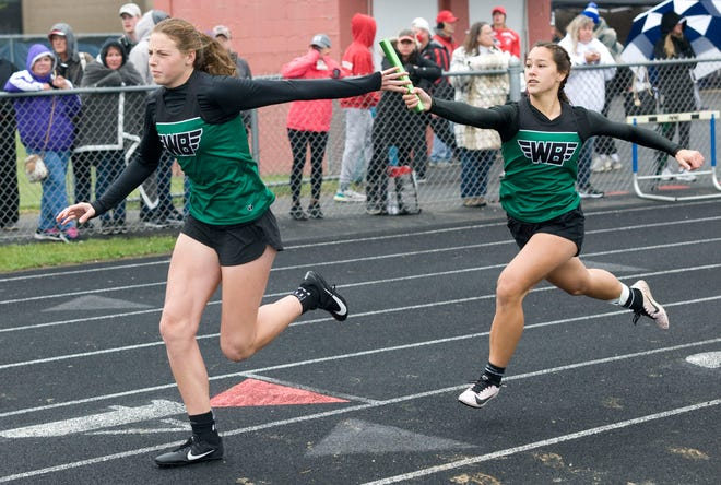West Branch's Sophia Gregory takes the baton from Lauren Gossett in the girls 4x200 meter relay during the DII Regional Track Championships at Austintown High School Saturday, May 29, 2021.