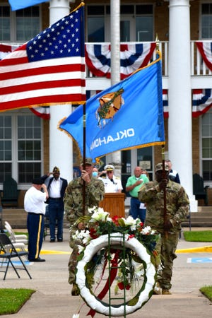 SSG Benjamin Miller and SPC Dennis Gay, U.S. Army Reserve 401st Engineer Company from Mustang, retire the colors after a Memorial Day ceremony Friday, May 28, 2021.
