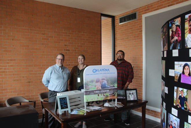 A display featuring information about the Oklahoma Fosters Program is on display inside the lobby at the Goddard Center Art Studio. The Goddard Center has partnered with the Foster Parent Exclusive Benefit Program for almost two years and offers free classes for foster children. From left to right: Goddard Center Executive Director Ken Bohannon, Oklahoma Child Welfare Specialist Holly Johnson, Goddard Center Art Studio Manager Joshua Tuaila.