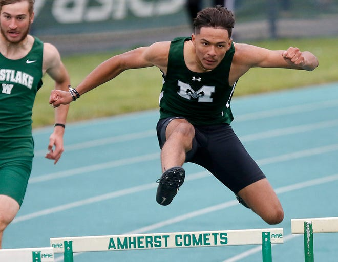 Madison's Isaac Brooks competes in the 300-meter hurdles at the Division I Amherst Regional track meet Friday at Amherst Steele High School. Brooks won the event.