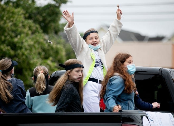 Evie DeLong, 11, waves to the crowd with her fellow softball teammates as the Grandview Heights Memorial Day Parade makes its way down First Avenue on Saturday. Last year's parade was canceled due to the COVID-19 pandemic.